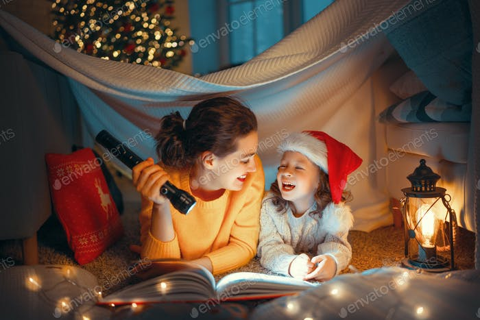 mother reading book to daughter near Christmas tree