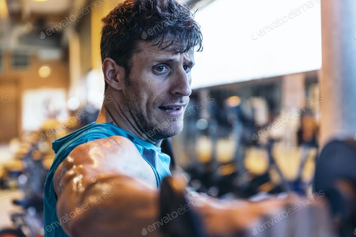 Fitness, workout, gym, lifestyle concept. Man training in club gym.