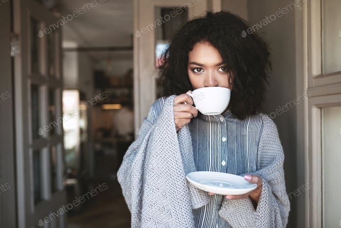 Beautiful lady with dark curly hair standing with cup of coffee in restaurant