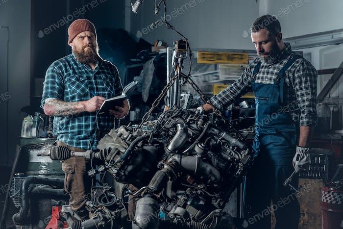 Zwei bärtige Männer reparieren Auto in einer Garage.