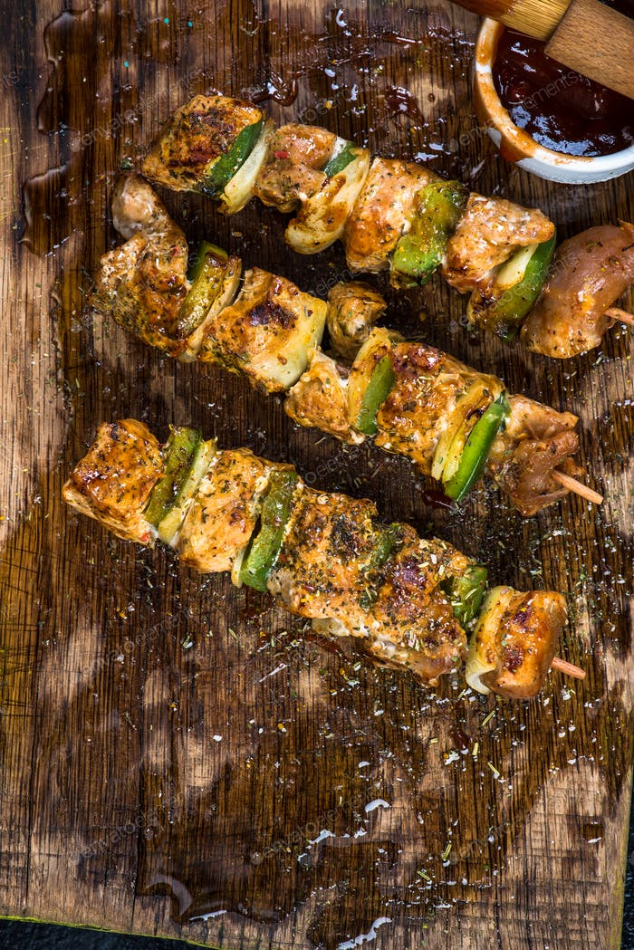 Grilled meat and vegetable skewers on wooden board
