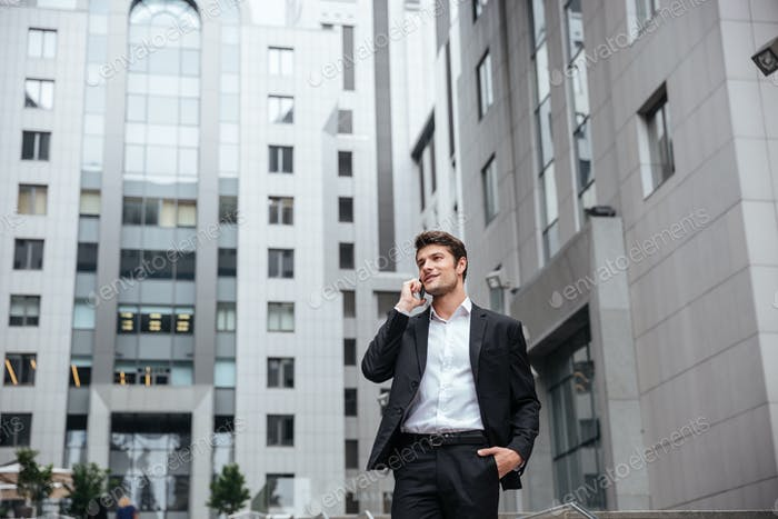 Businessman talking on mobile phone in the city