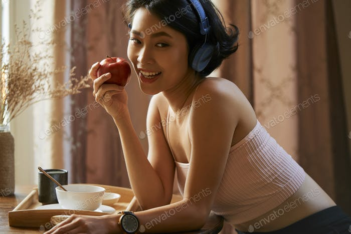 Pretty woman eating red apple