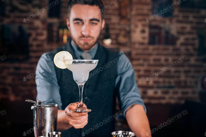 Handsome bartender, barman serving fresh made alcoholic beverage, margarita cocktail