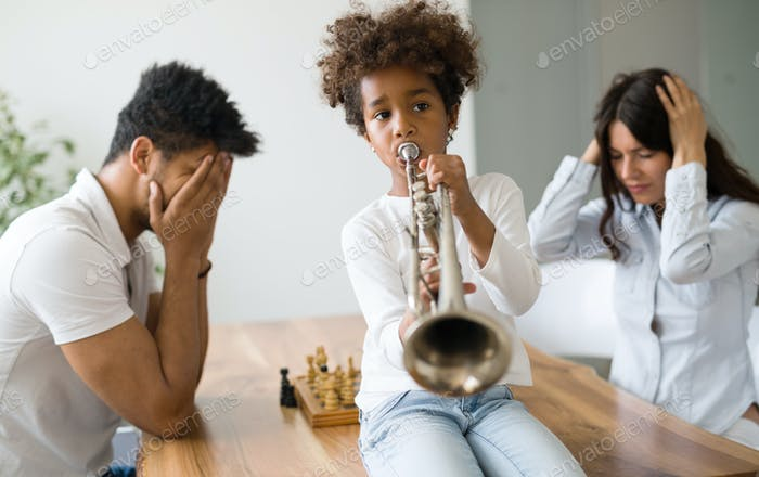 Mother and father trying to play chess while their child plays trumpet