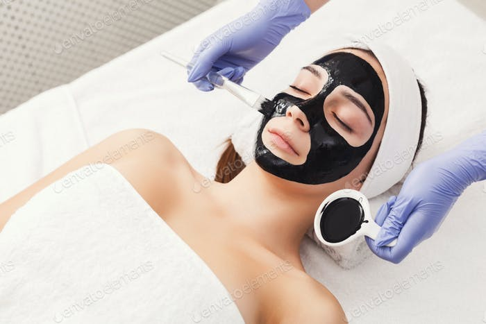 Woman getting face mask by beautician at spa