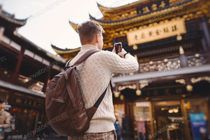male tourist taking photos of a pagoda at Yuyuan market in Shanghai