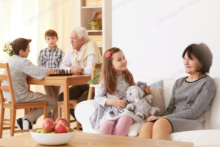 Little girl talking with grandmother in living room
