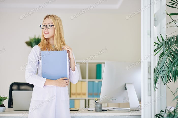 Young doctor holding medical history