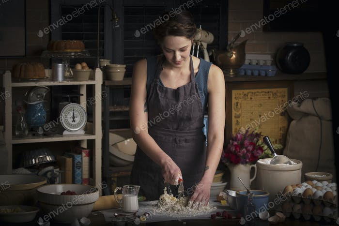 Valentine's Day baking, young woman standing in a kitchen, preparing dough for biscuits.