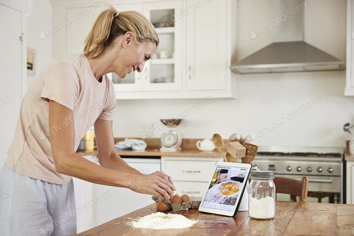 Woman Following Recipe On Digital Tablet In Kitchen