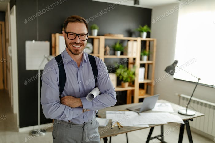 Portrait of young architect looking at camera in office.