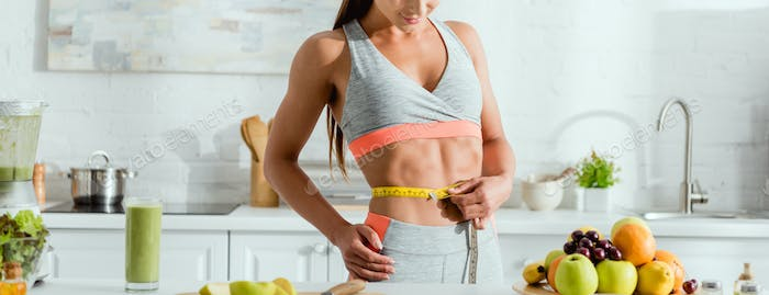 panoramic shot of sportive woman measuring waist near fruits