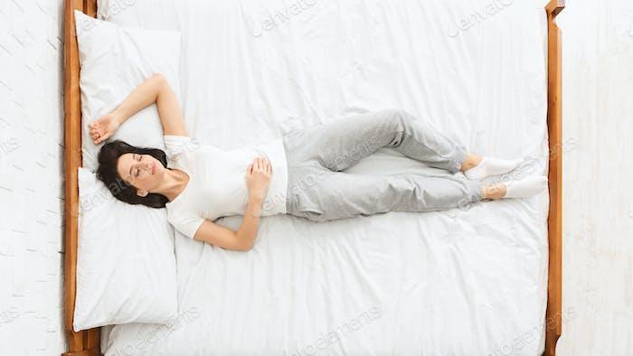 Millennial woman sleeping in bed,, top view