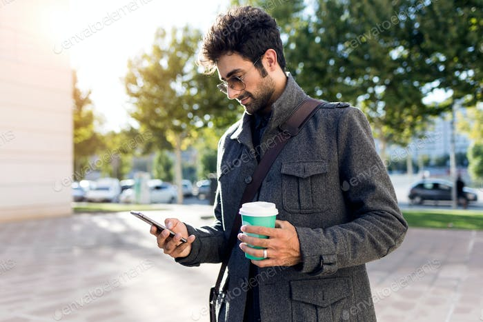 Modern young man using his mobile phone in the street.