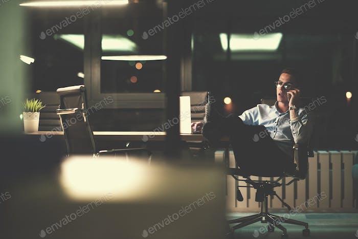 Empresario usando el teléfono Móvil en la oficina Oscuro