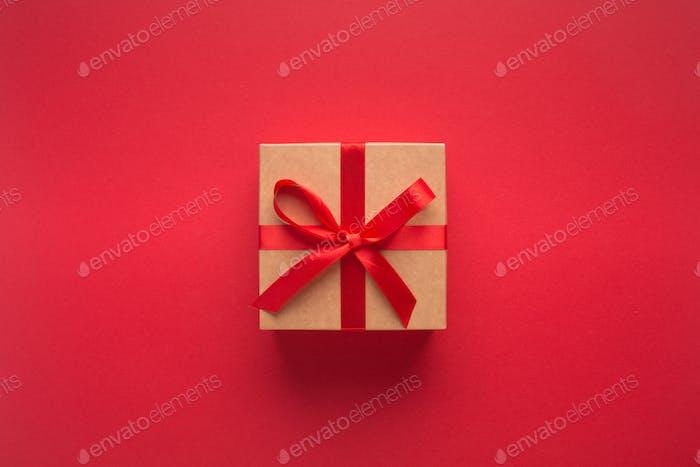 Neujahrsgeschenk mit Band isoliert auf rotem Hintergrund