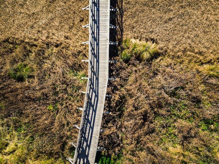 Wooden bridge over dry grassland,aerial view. Zelenci,Slovenia