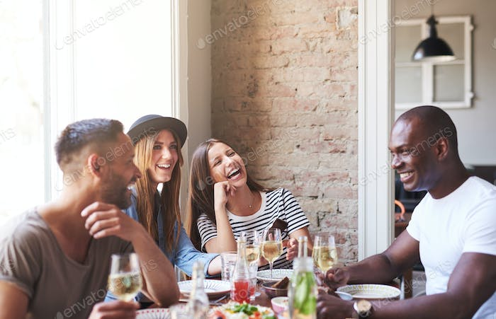 Four happy friends having wine and dinner together