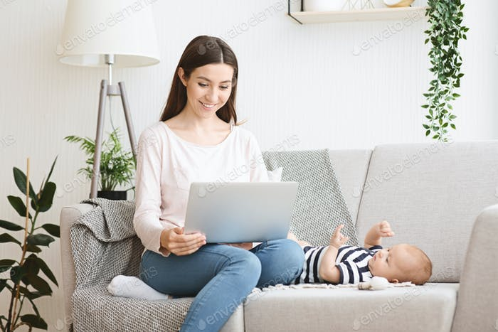 Hermosa joven madre leyendo blog del bebé en la computadora portátil