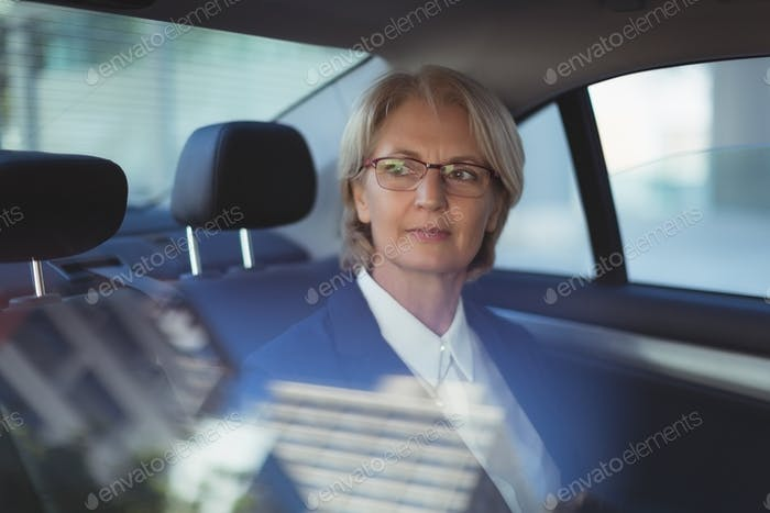 Thoughtful businesswoman traveling in car