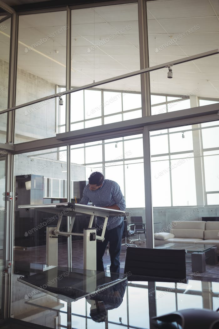 Male interior designer drawing on workbench in office