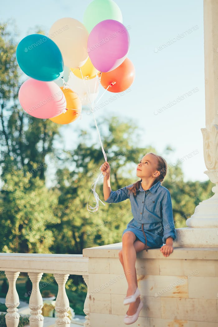 Girl holding colorful balloons looking to them while sitting in