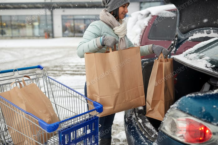 woman loading food from shopping cart to car trunk