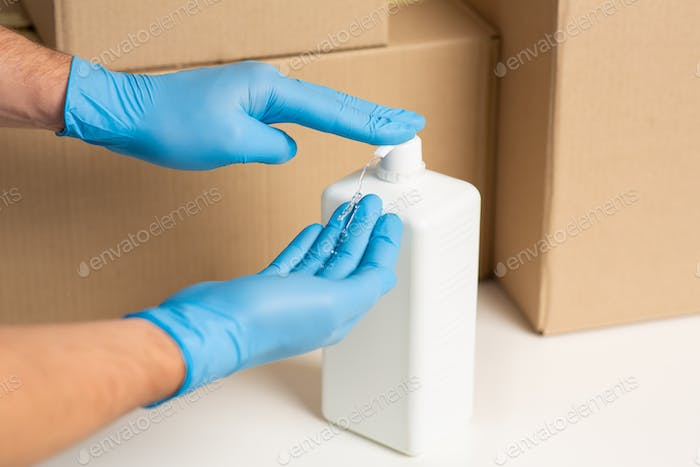 Deliveryman disinfects hands. Cardboard boxes at background