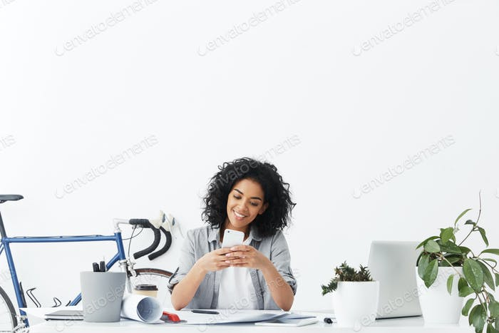 Attractive cheerful young student architect with Afro hairstyle using wifi on smart phone for messag