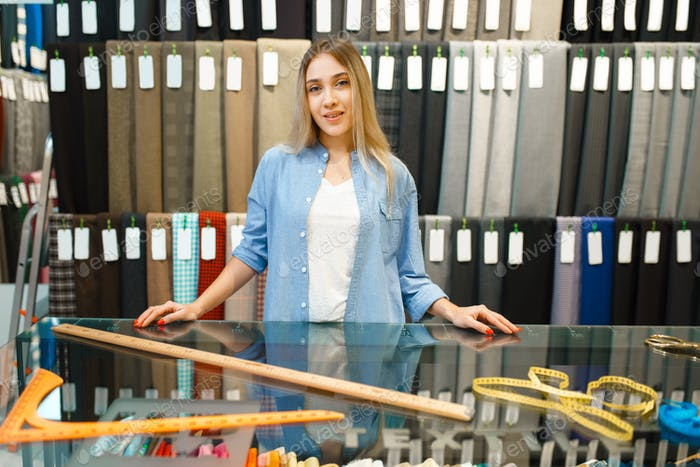 Woman measures the fabric in textile store