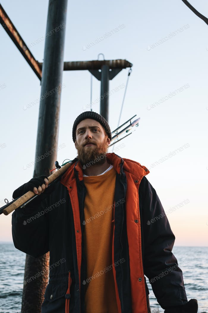 Handsome brutal bearded fisherman wearing coat