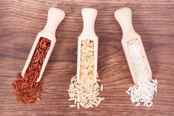 Roter, brauner und weißer Reis mit Holzlöffel auf rustikalem Brett