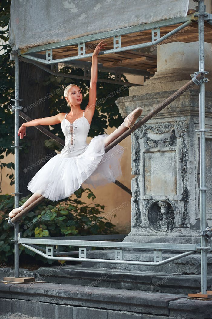 Ballerina dancing near building under construction
