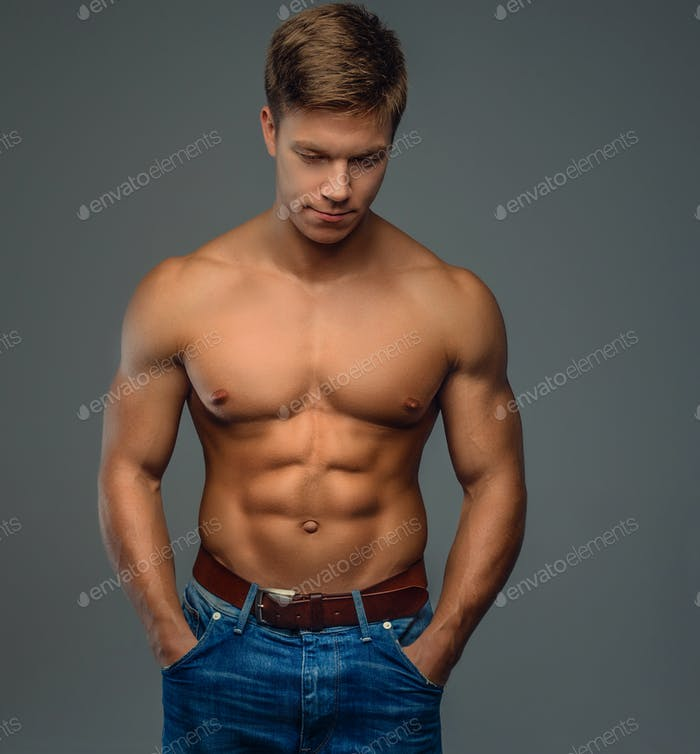 Shirtless muscular young man in denim jeans.