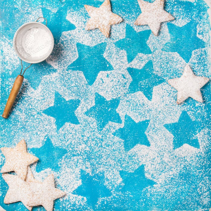 Heart shaped cookies with sugar powder and sieve, blue background