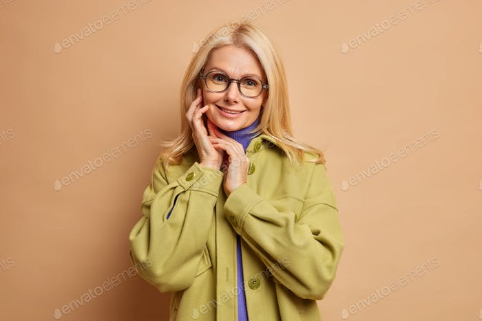 Fashionable lovely blonde woman touches face gently looks directly at camera has healthy skin and mi