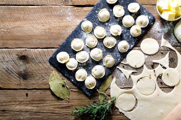 Ingredients for making pelmeni, ravioli, dumplings - dough, rosemary, rolling pin, canvas thread