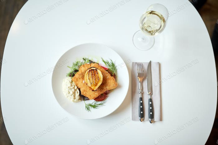 fish salad and wine glass on restaurant table