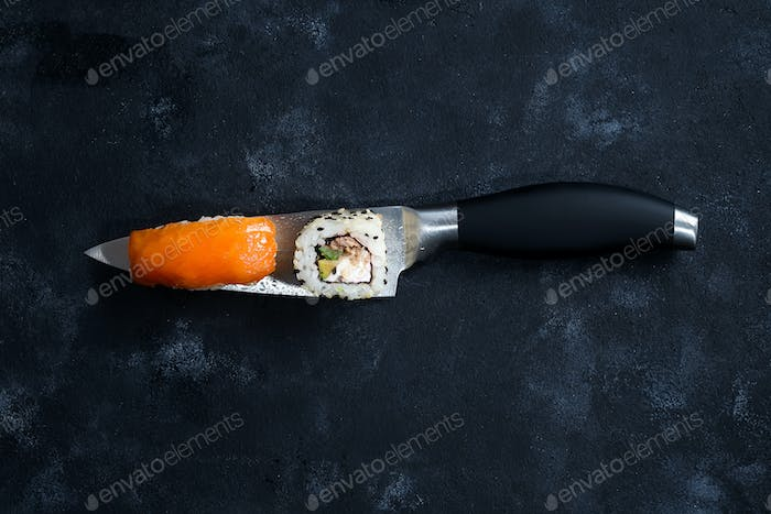 Different Sushi served on japanese knife on a black slate plate . flat lay