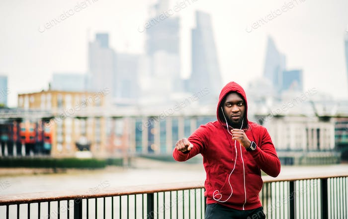 A black man runner with earphones and hood on his head in a city. Copy space.