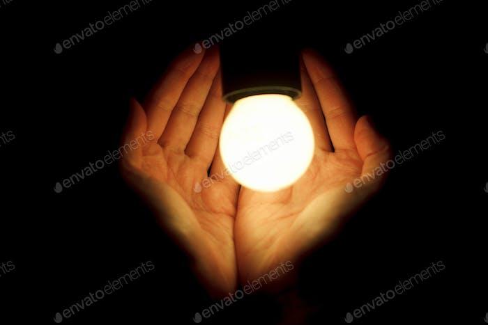 hands of human holding illuminated led bulb on black background