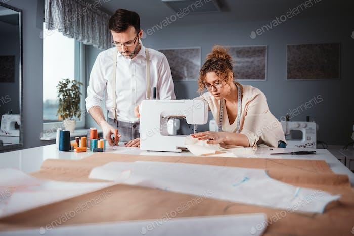 Sastres profesionales durante el trabajo en el proyecto en el estudio de diseño de moda