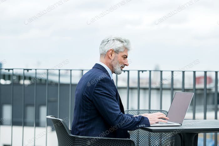 A mature businessman with laptop sitting on a terrace, working.