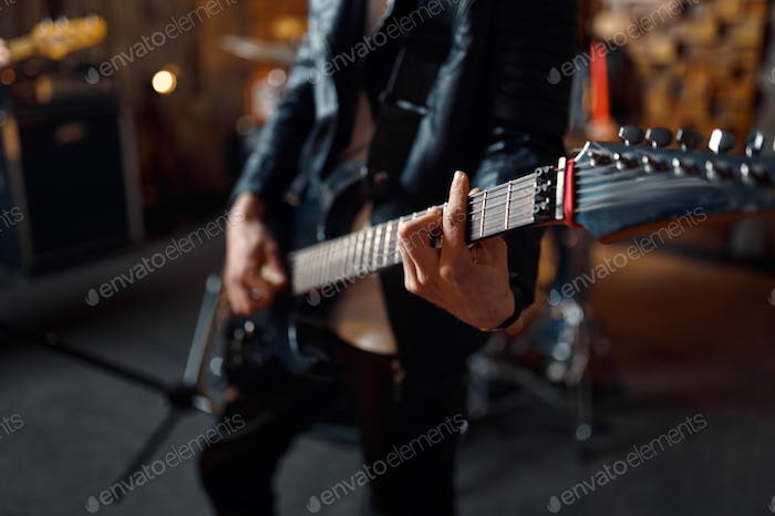 Brutal guitarist with electric guitar on stage