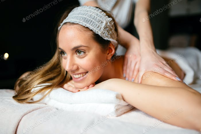 Beautiful young and cute woman enjoying massage treatment