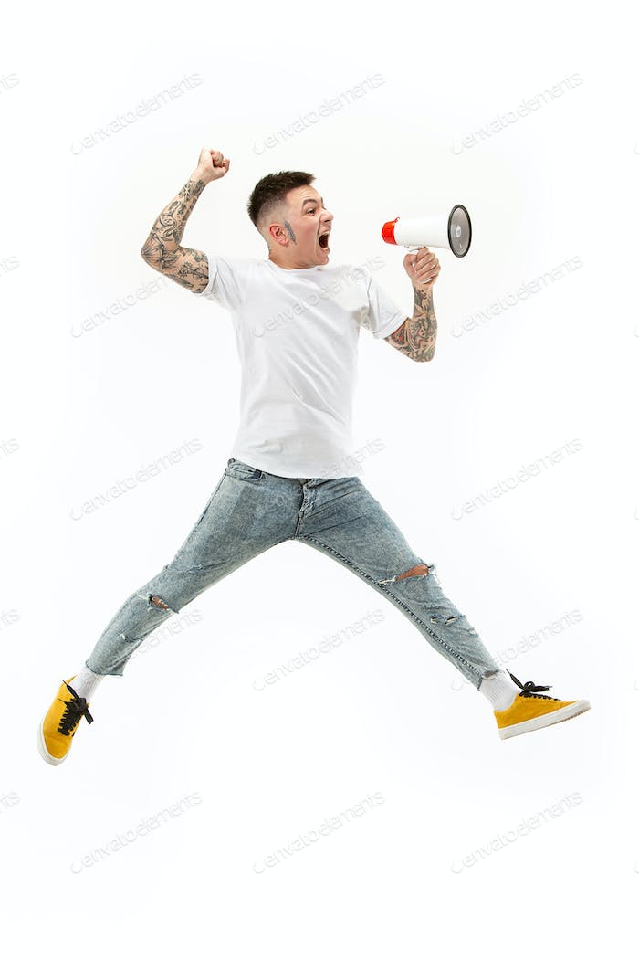 Jumping fan on white background. The young man as soccer football fan with megaphone