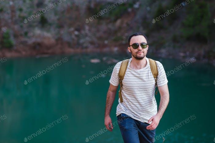 Bearded man model poses alongside a Green water Lake.