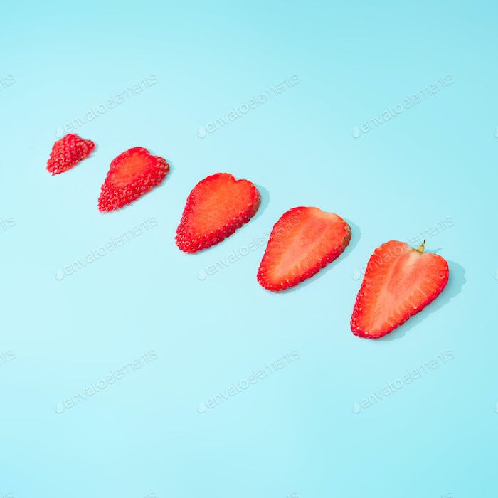 Creative summer background composition with strawberry slices. Minimal fruit concept.