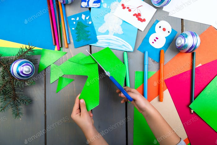 Child hands make handmade christmas toys from cardboard. Children's DIY concept.
